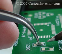 Curved tweezers holding a 1206 resistor